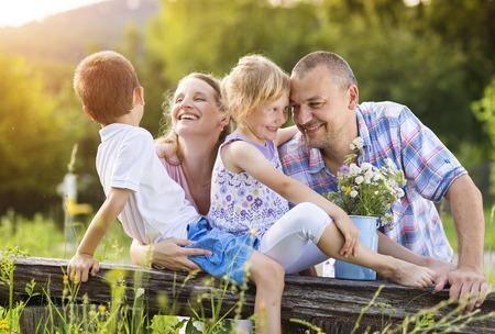 mama e hijo: Feliz familia joven pasar tiempo juntos fuera en la naturaleza verde tiempo.