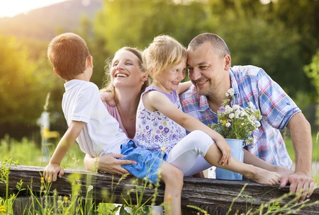 young mother: Happy young family spending time together outside in green nature. Stock Photo