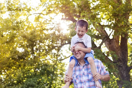 uomo felice: Padre felice con suo figlio trascorrere del tempo insieme al di fuori in natura verde.