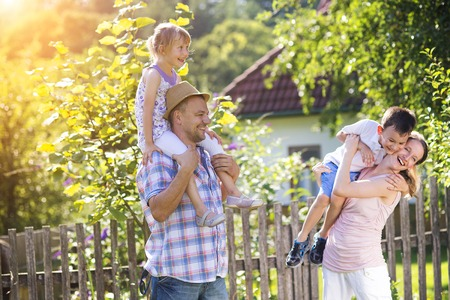 children at play: Happy young family spending time together outside in green nature. Stock Photo