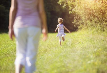 niño corriendo: Madre feliz con su hija pasar tiempo juntos fuera en la naturaleza verde. Foto de archivo