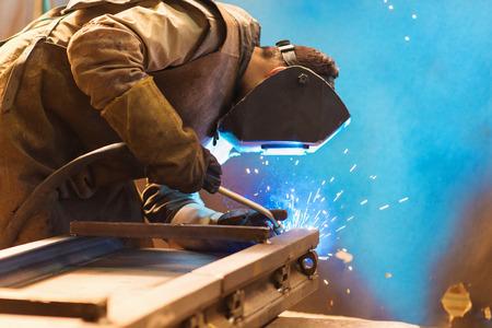 Junger Mann mit Schutzmaske Schweißen in einer Fabrik Standard-Bild - 40551928