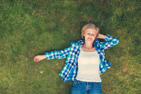 Beautiful senior woman lying on a grass in a park Stock Photo