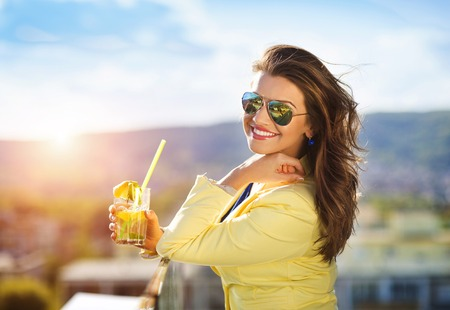 Attractive young woman with a drink on a terrace of a bar Stock Photo