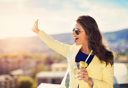 bar top: Attractive young woman with a drink on a terrace of a bar Stock Photo