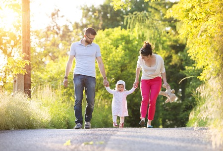 Happy young family having fun outside in spring nature Stock Photo