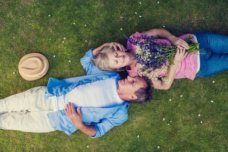 Mooie senioren liggend op een gras in een park knuffelen