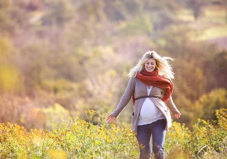 embarazada: Retrato de la hermosa mujer embarazada en un campo