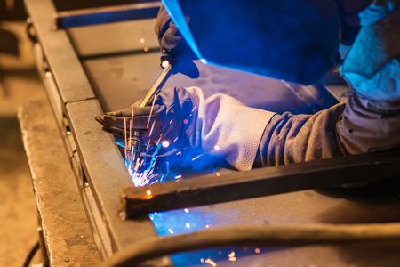 soldadura: Hombre joven con la máscara protectora de soldadura en una fábrica