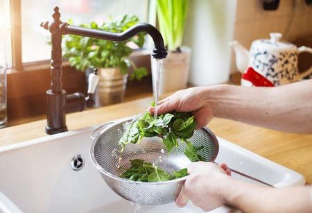 Unrecognizable man washing green salad leaves in the kitchen sink Stockfoto