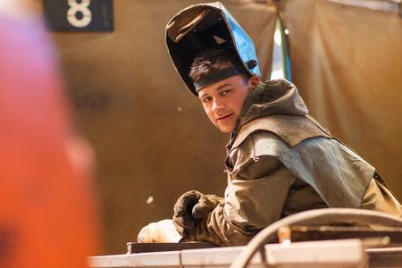 soldador: Hombre joven con la máscara protectora de soldadura en una fábrica
