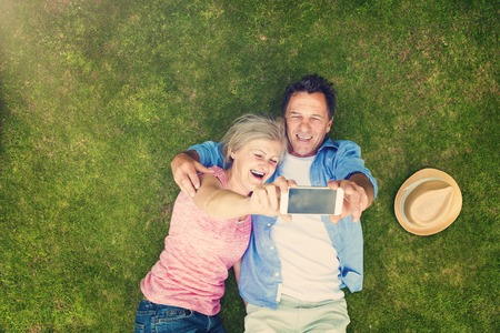 Belles personnes âgées se trouvant sur l'herbe dans un parc étreindre Banque d'images
