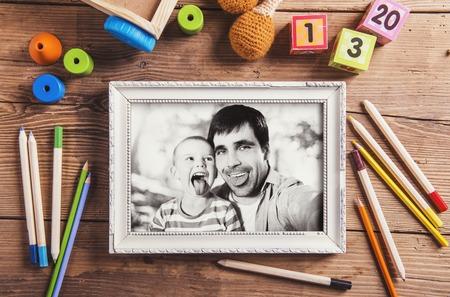 padres: Padres composición días - juguetes en el piso. Estudio tirado en el fondo de madera. Foto de archivo