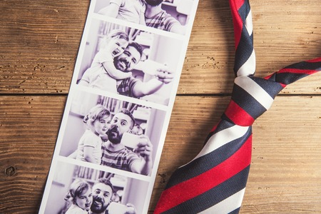 Pictures of father and daughter and colorful tie laid on wooden floor backround.