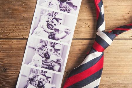 lazo regalo: Fotos de padre e hija y colorido empate pusieron en antecedentes suelo de madera. Foto de archivo