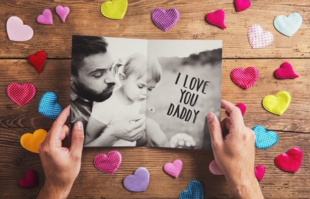 father with child: Fathers day composition - textile hearts on the floor. Studio shot on wooden background.