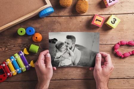 ni�os felices: Padres composici�n d�as - juguetes en el piso. Estudio tirado en el fondo de madera. Foto de archivo