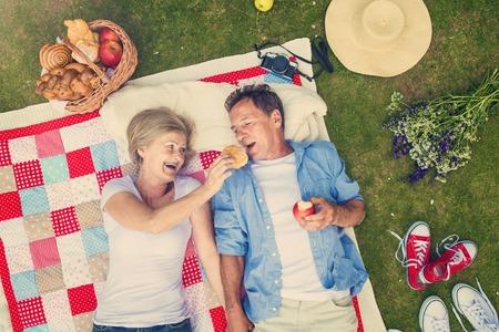 Beautiful seniors having a picnic in nature