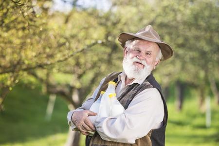 milk mustache: Senior farmer with milk bottles outside in green nature Stock Photo