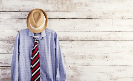 Fathers day composition of shirt, tie and hat hang on wooden wall background. photo