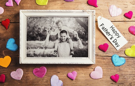 black picture frame: Fathers day composition - picture frame and colorful hearts on the floor. Studio shot on wooden background.