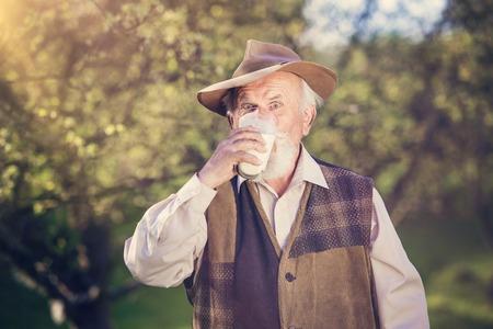milk mustache: Senior farmer with a glass of milk outside in green nature Stock Photo