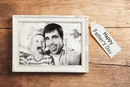 picture person: Fathers day composition - picture frame with a black and white photo. Studio shot on wooden background. Stock Photo