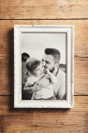 black picture frame: Fathers day composition - picture frame with a black and white photo. Studio shot on wooden background. Stock Photo