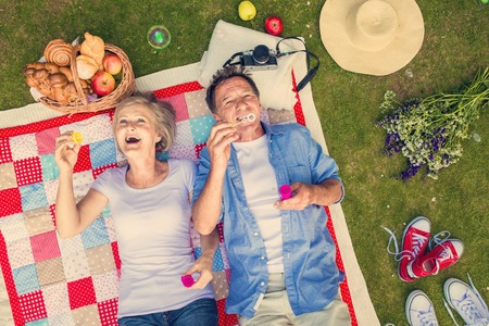 Beautiful seniors having a picnic in nature and blowing bubbles Stock Photo