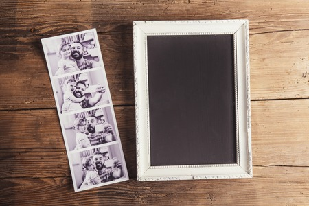 Picture frame and instant photos on wooden background. Фото со стока