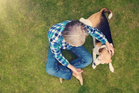 pet therapy: Beautiful senior woman lying on a grass in a park Stock Photo