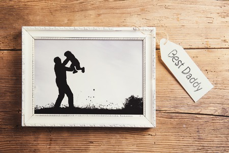 black and white image: Fathers day composition - picture frame with a black and white photo. Studio shot on wooden background. Stock Photo