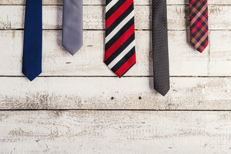 Fathers day composition of various ties hang on wooden wall background.