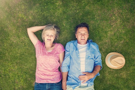 couple relaxing: Beautiful seniors lying on a grass in a park