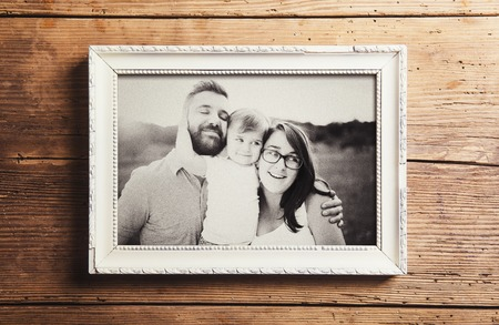 Fathers day composition - picture frame with a black and white photo. Studio shot on wooden background. Stockfoto