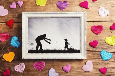 아버지의 날 컴포지션 - 사진 프레임과 바닥에 다채로운 마음입니다. 스튜디오 나무 배경에 총.