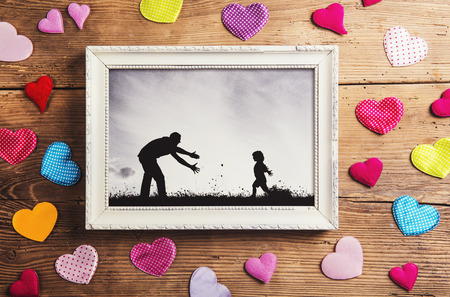 picture frame on wall: Fathers day composition - picture frame and colorful hearts on the floor. Studio shot on wooden background.