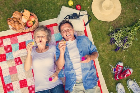 blows: Beautiful seniors having a picnic in nature and blowing bubbles Stock Photo