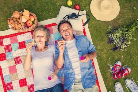 Mooie senioren met een picknick in de natuur en bellen blazen