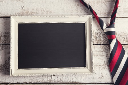 Rectangle picture frame and colorful tie laid on wooden floor backround. Stock Photo