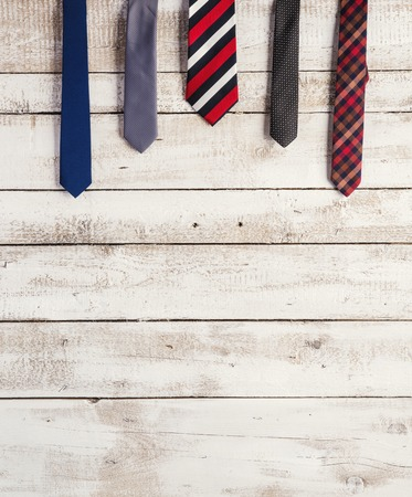 red tie: Fathers day composition of various ties hang on wooden wall background.
