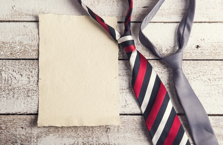 tie: Fathers day composition - ties and empty sheet of paper. Studio shot on wooden background. Stock Photo