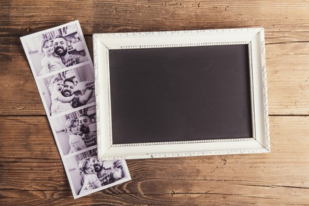 Picture frame and instant photos on wooden background. Stockfoto