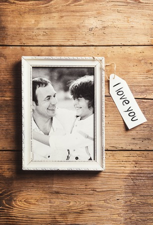 love message: Fathers day composition - picture frame with a black and white photo. Studio shot on wooden background. Stock Photo