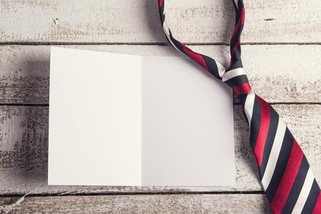 day: Padres composición días - corbata y la hoja de papel en blanco. Estudio tirado en el fondo de madera.
