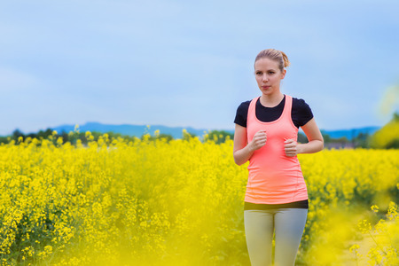 woman in field: Beautiful young woman running outside in spring canola field Stock Photo