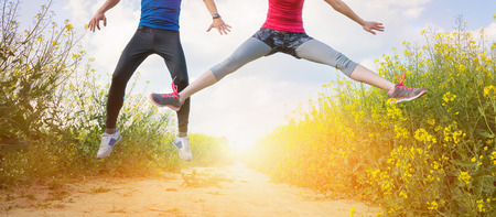 fitness hombres: Corredores jovenes que se divierten en el campo de canola de primavera