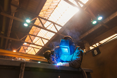 protective spectacles: Young man with protective mask welding in a factory Stock Photo