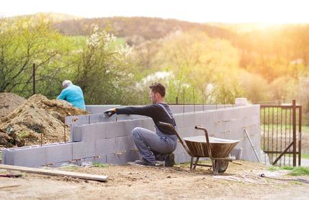 builder: Alba�il sofocar otra fila de ladrillos en el sitio