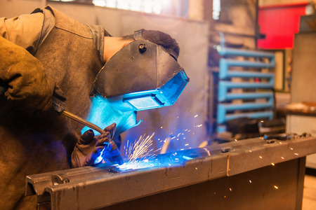 Young man with protective mask welding in a factory 스톡 콘텐츠